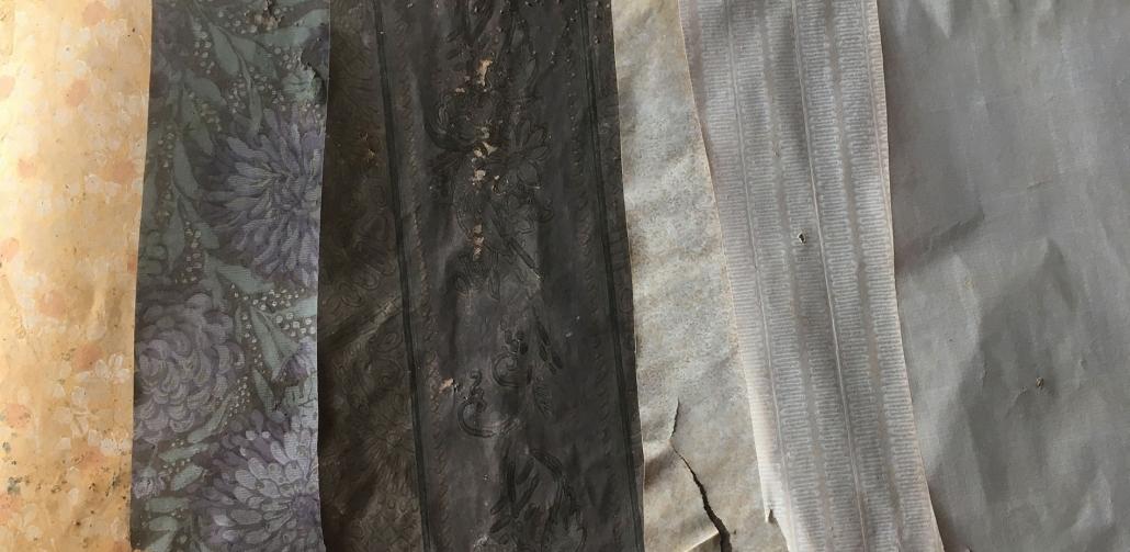 Tapettifragmentit on irrotettu toisistaan. Vanhin kerros on kuvassa vasemmalla.