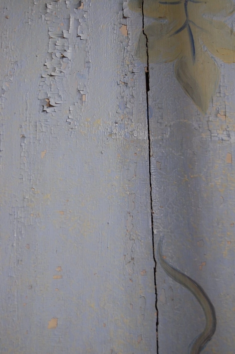 Toholammin kirkon seinämaalaus konservointitöiden aikana. Kuvan alaosassa on kiinnitettyä värikerroksia, yläosaan ei ole tehty toimenpiteitä.
